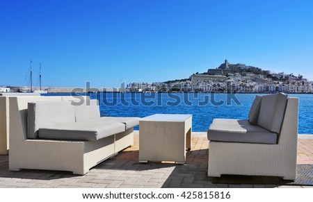 empty couches at the Mediterranean Sea, with Sa Penya and Dalt Vila districts, the old town of Ibiza Town in the background, in the Balearic Islands, Spain