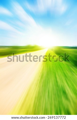 Empty country road in motion blur and sunlight. - stock photo