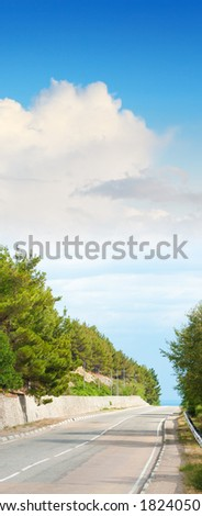Empty countryside road and blue sky - stock photo