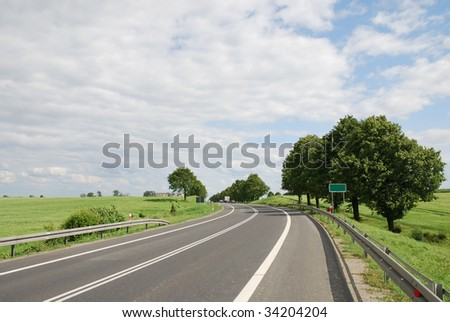 Empty countryside road at summer day - stock photo