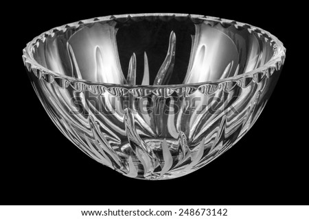 Empty crystal rounded salad bowl on black background - stock photo