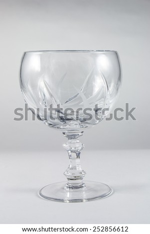 Empty crystal wine glass on a gray background - stock photo