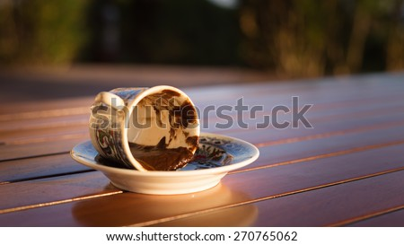 Empty cup after turkish coffee in direct sunset light - concept of traditional way of fortunetelling. Shallow DOF and lightly toned - stock photo