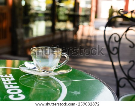 Empty cup  of  coffee  on  green  table  after  relax  within  coffee  break  time. - stock photo
