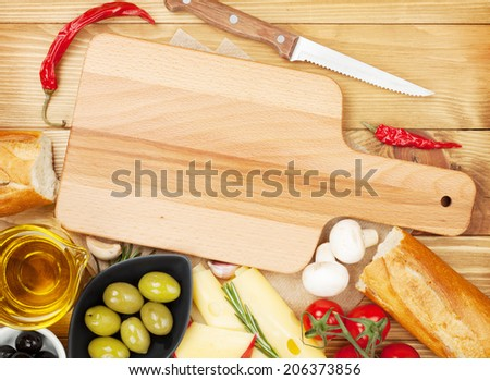 Empty cutting board for copy space and various food - stock photo