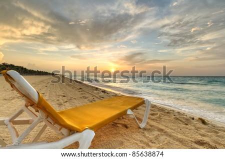 Empty deckchair on the Caribbean Sea at sunrise - stock photo