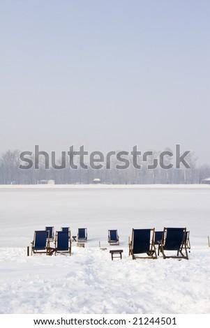 empty deckchairs on a frozen lake - stock photo