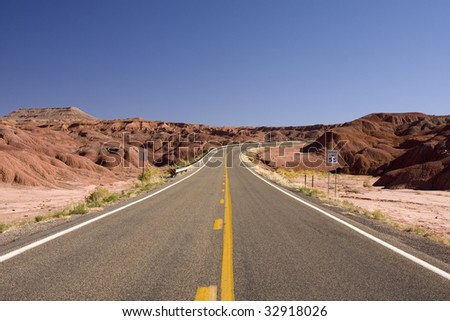 Empty Desert Highway in Utah with Mountains - stock photo