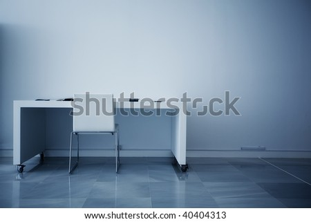 Empty desk facing white wall.