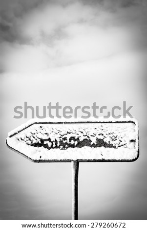 empty directional road sign, pointing arrow with snow in winter season - stock photo