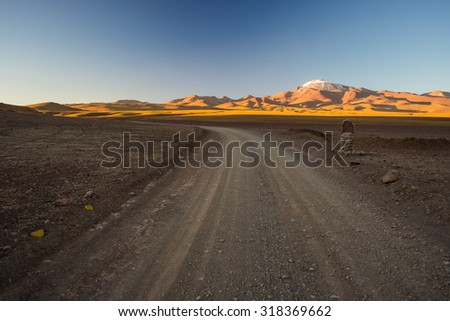 Empty dirt road on high altitude barren mountain range on the highlands of the Andes on the way to the famous Uyuni Salt Flat, among the most important travel destination in Bolivia. - stock photo