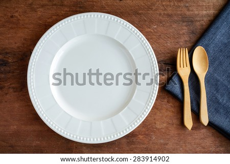 Empty dish with wooden spoon and fork on old wood, Top view - stock photo