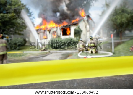 "Empty ""do not cross"" tape with firefighters and a burning house in the background - stock photo"