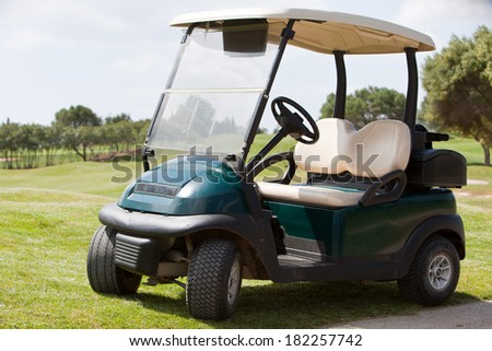 Empty electric golf cart parked on a fairway at a golf club in the hot summer sunshine - stock photo