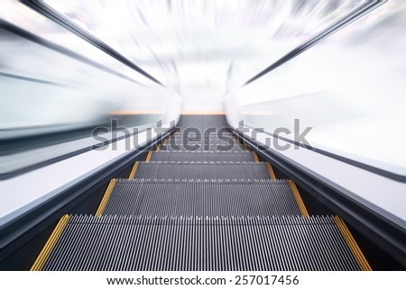 Empty escalator going down with motion blur - stock photo