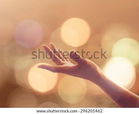 Empty female open human left hand with palms up and golden candle night lights bokeh in natural warm gold color tone: Pray for spiritual support, destiny, power and helping concept: Orange the world   - stock photo