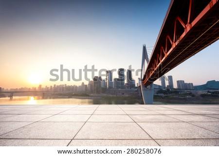 Empty floor in front of skyline and bridge - stock photo