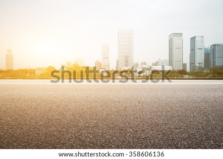 empty floor with backdrop on modern cityscape at sunrise time - stock photo