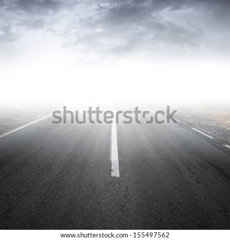 Empty foggy rural asphalt highway perspective with white line - stock photo