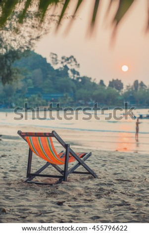 Empty folding lounge chair on the sand beach. Sunset sunrise time. Soft shadows. Vacation wallpaper. Travel inspiration. Postcard concept. Vintage effect.