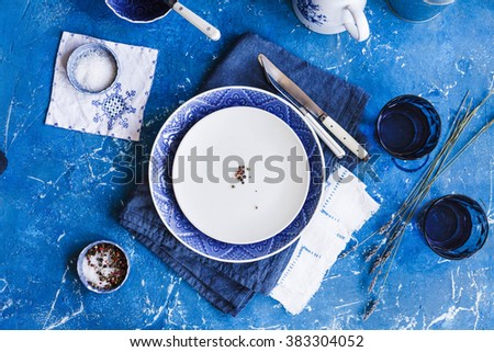 Empty food tableware, ceramic plate, spice little bowls, knife, fork with a old linen cloth on a old vintage stone table. Country blue styling. Top view. - stock photo