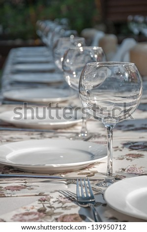 empty footed tumblers,glasses and party plates on festive served table