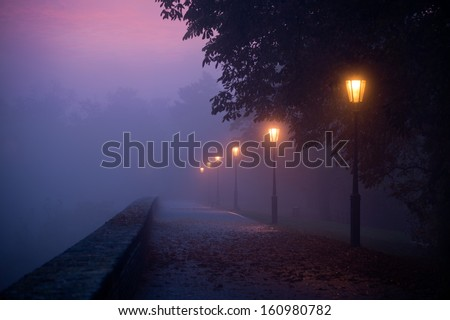 Empty footpath in morning mist with colored sky visible - stock photo