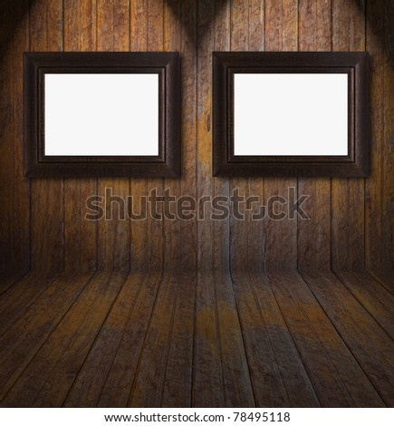 Empty frames in a room against wooden wall - stock photo