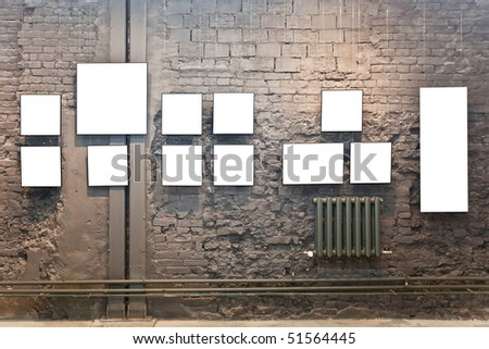 Empty frames on brown brick wall in museum - stock photo