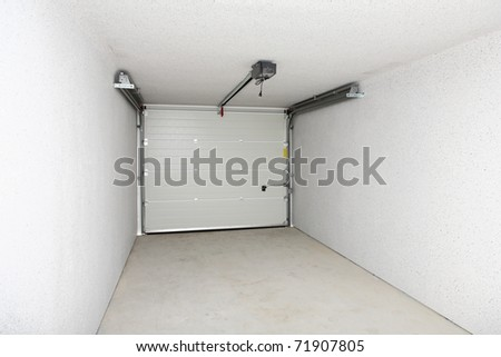 Empty garage or warehouse with closed door - stock photo