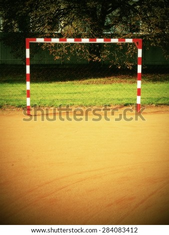 Empty gate. Outdoor football or handball playground, dry red crushed bricks surface on ground - stock photo