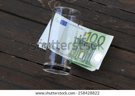 Empty glass and one hundred Euro banknotes on wooden table - stock photo