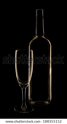 Empty glass and wine bottle composition in low-key lighting over the black background - stock photo