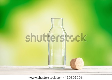 Empty glass bottle with a cork on green background - stock photo