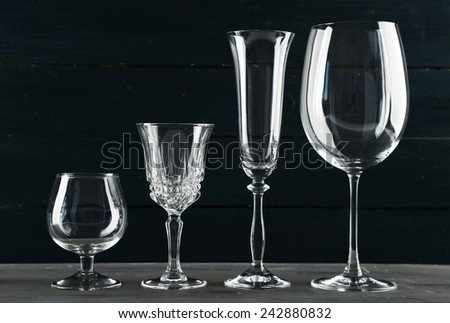 Empty glass goblets on dark color wooden background - stock photo
