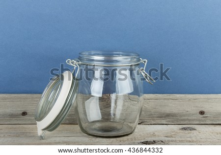 Empty glass jar with cap hold with metal wire  on the wooden floor - stock photo