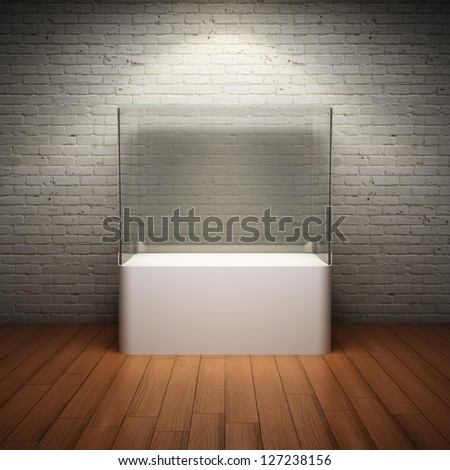 Empty glass showcase for exhibit in interior room with brick wall and spotlight - stock photo