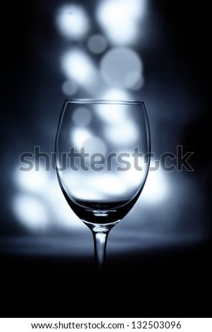 Empty Glass with Light Bokeh in Background. Small depth of field. - stock photo