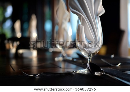 Empty glass with napkin and silverware on table for dinner setting - stock photo