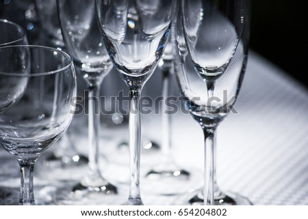 Empty glasses arranged on a table in the restaurant, cafe, or bar. Preparation for the birthday, wedding, or any celebration day.