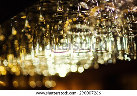 Empty glasses hanging over in restaurant bar - stock photo