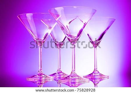 empty glasses of martini on purple background - stock photo