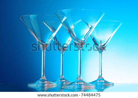 empty glasses of martini on the light blue background - stock photo