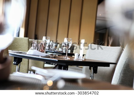 Empty glasses set in restaurant, Defocused foreground , Ambient lighting - stock photo