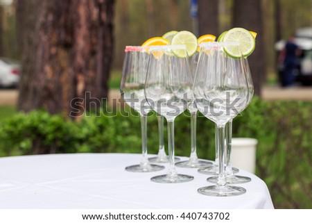 Empty glasses with slices of lime and lemon, decorated sugar standing by the table. Prepared for the lemonade. - stock photo