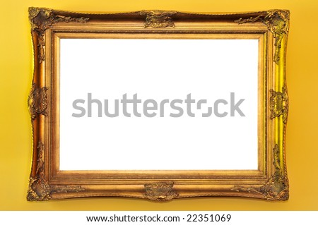 Empty gold picture frame on yellow wall - stock photo