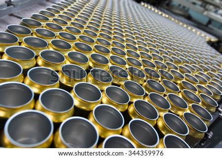 Empty golden beverage cans on the conveyor belt - stock photo
