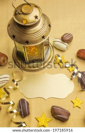 Empty golden plaque with Ramadan lantern and date chocolates - stock photo