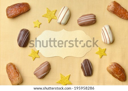 Empty golden seal surrounded by date chocolates and dates - stock photo