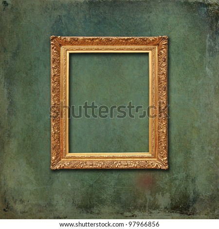 Empty golden vintage frame on a scratched grunge wallpaper with faded design. - stock photo